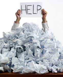person, surrounded by crumpled writing paper, holding up help sign